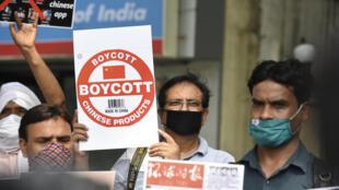 """Des membres de Working Jounalists in India (WJI) tiennent des placards appelant les citoyens indiens à supprimer les applications chinoises pour smartphone et à boycotter les produits """"made in China"""", lors d'une manifestation à New Delhi, le 30 juin 2020."""