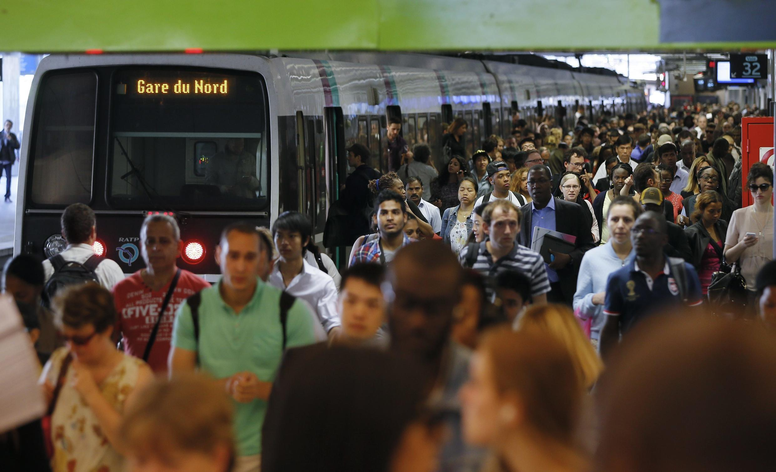 Crowds get off a commuter train at Gare du Nord railway station in Paris, 13 June
