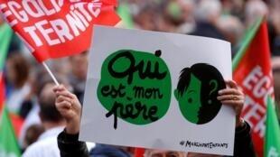 """Manifestante exibe cartaz com a mensagem: """"Quem é o meu pai?"""", durante protesto neste domingo (6), em Paris, contra a extensão da reprodução medicamente assistida a casais de lésbicas e mulheres solteiras."""