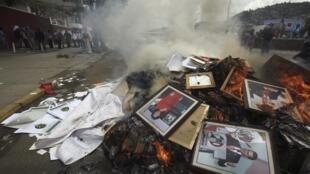 Fotos del presidente Enrique Peña Nieto y de representantes del partido presidencial quemadas por miembros del sindicato de maestros CNTE, en Oaxaca.
