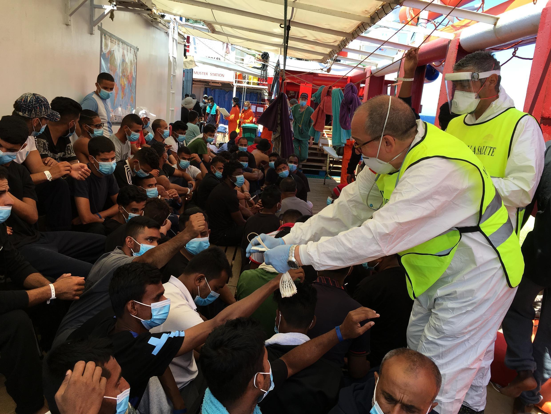 Un trabajador sanitario italiano entrega pulseras numeradas a los migrantes rescatados en el mar en el barco humanitario 'Ocean Viking', el 5 de julio de 2020 en el Mar Mediterráneo