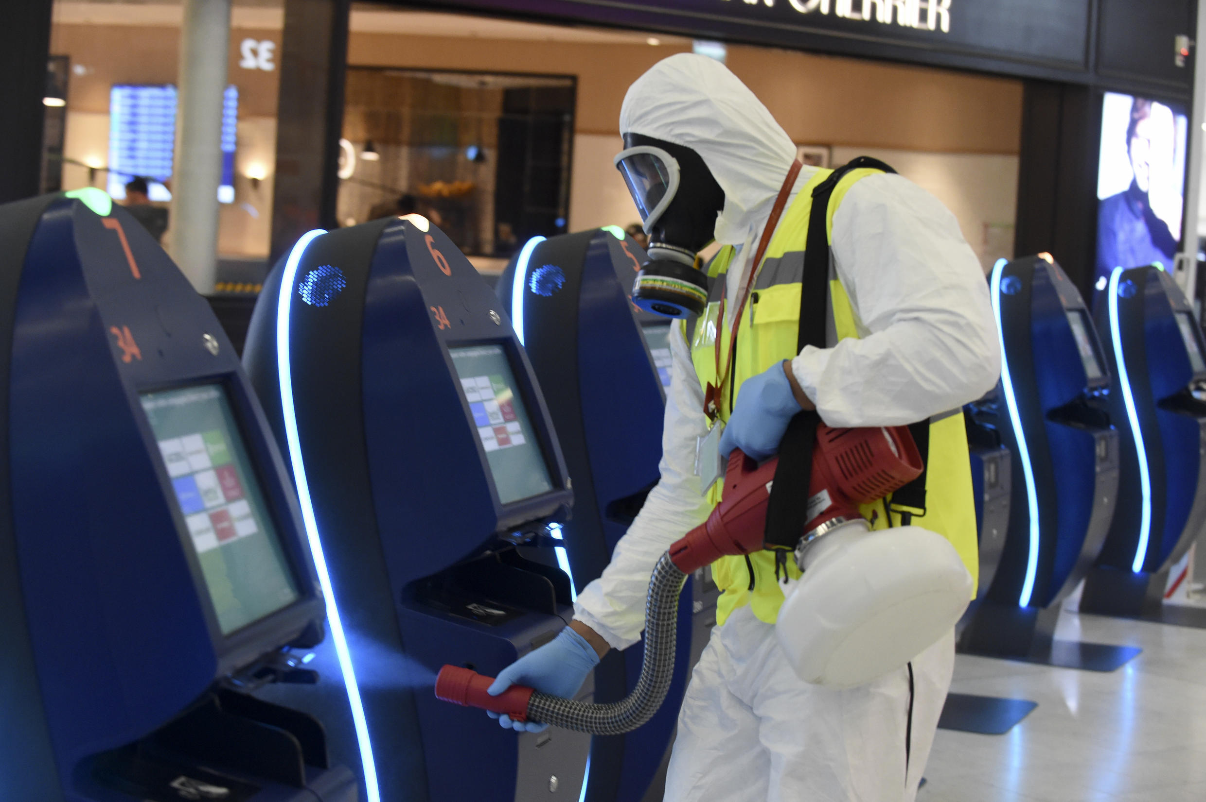 An operator disinfects self-service check-in kiosks at Orly 3 terminal's departure hall on the day of the re-opening of Paris' Orly airport on June 26, 2020.
