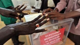 Election locales le 22 mars 2009 dans un bureau de vote de Dakar : cette électrice montre ses mains exemptes de marque d'encre pour pouvoir voter.
