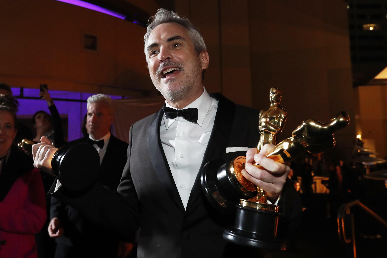 El mexicano Alfonso Cuarón con su tres estatuillas, el domingo en Hollywood.
