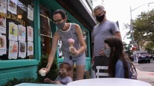 Les membres d'une même famille portent le masque pour se protéger de l'épidémie, dans le quartier de Brooklyn à New York, le 15 juillet 2020.