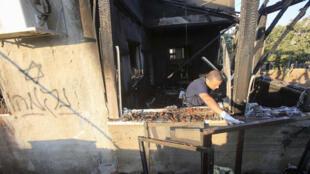 Un policía israelí inspecciona el lugar del incendio atribuido a judíos extremistas en Kafr Duma, 31 de julio de 2015.