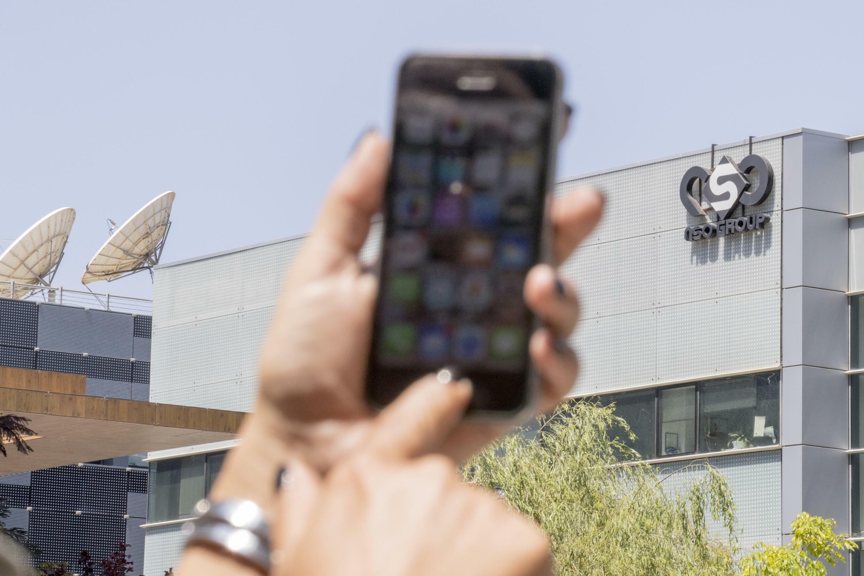 Un persona usa su celular frente a la firma israelí NSO, creada en 2011 y acusada en múltiples ocasiones de colaborar con regímenes autoritarios, en especial desde que en 2016 el opositor emiratí Ahmed Mansoor alertó sobre este tipo de prácticas