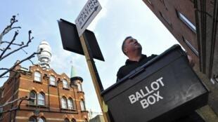 Un miembro del servicio electoral británico distribuye los votos para el referedum que mantiene dividida a la coalición de gobierno y genera dudas sobre su durabilidad.