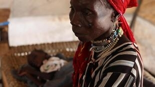 A woman sits on the bed next to her malnourished child at Doro refugee camp in South Sudan, 9 March, 2012