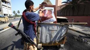 Um rebelde líbio rasga uma fotografia de Kadhafi