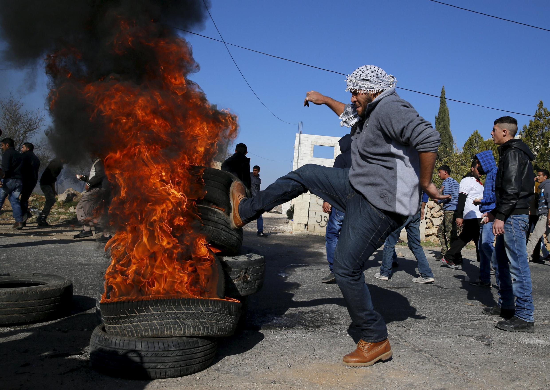 Manifestante palestino queima pneu em protesto em Silwad, Cisjordânia.