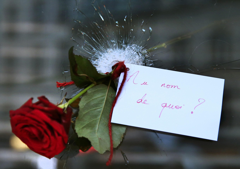 """""""Em nome de quê?"""", diz a mensagem, junto a uma rosa, colocadas no buraco de um tiro dos atentados em Paris."""