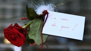 Une rose fichée dans un impact de balle sur la vitre d'un restaurant visé lors des attentats de Paris. «Au nom de quoi», peut-on lire sur la note qui l'accompagne.
