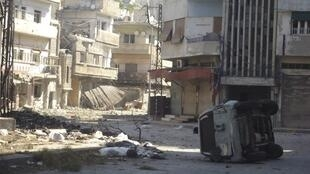 A damaged vehicle and buildings are seen in Karm Chmchm near Homs, 12 July  2012