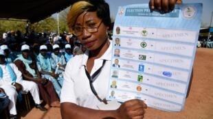 Uma agente eleitoral ostenta um boletim de voto relativo às eleições presidenciais de 22 de Fevereiro de 2020 no Togo.
