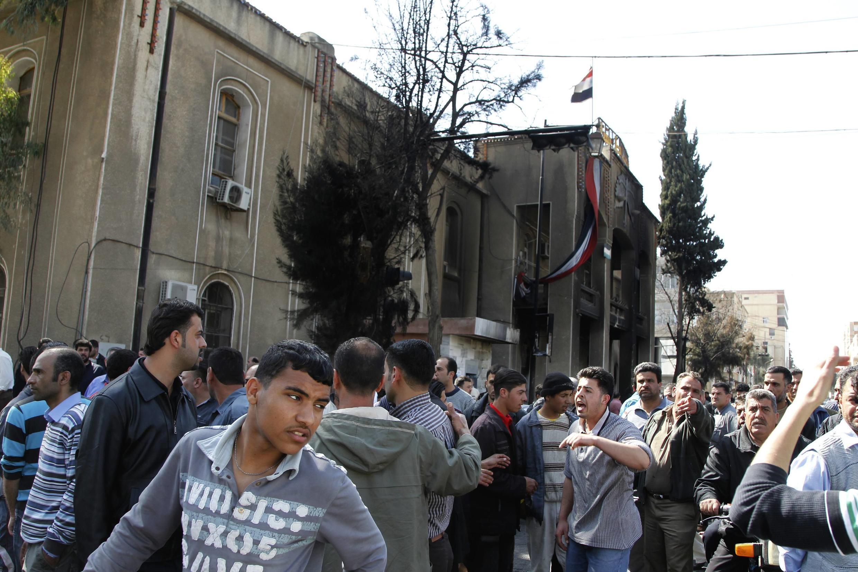 Rassemblement de manifestants contre la corruption en Syrie, devant le tribunal incendié de la ville de Deraa, le 21 mars 2011.