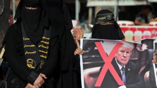 Uma mulher palestina segura um cartaz cruzado representando o presidente dos EUA, Donald Trump, durante um protesto contra a conferência do Bahrein para o plano de paz dos EUA, no sul da Faixa de Gaza em 18 de junho de 2019.