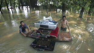 中國洪災地區居民儘力搶救自己的一些家中物品