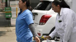 Empleados desinfectan su ropa fuera del laboratorio donde se realizan las pruebas COVID-19 en el Hospital Adolfo López Mateos en la Ciudad de México el 8 de mayo de 2020, en medio de la nueva pandemia de coronavirus