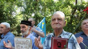 Les gens prient en commémorant l'anniversaire de la déportation des Tatars de Crimée de Crimée en Asie centrale en 1944, dans la capitale régionale Simferopol, en Crimée, le 18 mai 2018.