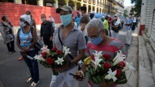 Les fans de la chanteuse et actrice de cinéma Rosita Fornes font la queue devant le théâtre Marti pour lui rendre hommage lors de ses funérailles à La Havane, le 16 juin 2020.