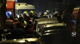Policiais em Toulouse diante do prédio do suspeito, no bairro mergulhado no escuro.
