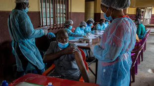A healthcare worker rolls up his sleeve to get the Ebola vaccine at N'Zérékoré hospital on 24 February 2021.