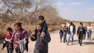 Des familles de migrants avec enfants, après avoir traversé le fleuve Rio Grande, marchent en direction des États-Unis, depuis le Mexique à Penitas, au Texas, le 6mars2021.