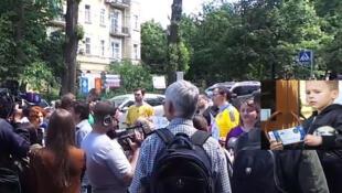 Des supporters ukrainiens rassemblés devant l'ambassade de France à Kiev, en attente de leurs visas Schengen. En médaillon, le petit  Volodia Bobentchik, tickets pour les matches en main. (Capture d'écran) lundi, 6 juin2016.