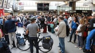 Anxious travellers wait for news of their trains at Paris Montparnasse railway station on Sunday