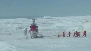 Helicóptero faz resgate de passageiros presos em navio na Antártida.