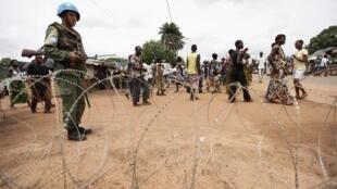 Les casques bleus des Nations unies gardent l'entrée d'un camp de réfugiés à Duékoué, Côte d'Ivoire.
