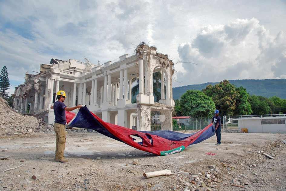 Déblaiement des ruines du Palais national qui faisait la fierté de tous les Haïtiens. Lors du chantier, les ouvriers ont pris soin de conserver, selon les honneurs, l'immense drapeau qui flottait au moment du séisme devant l'édifice.