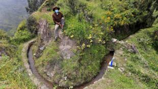 Un campesino se sienta junto a parte de una red de canales de piedra prehispánicos que surca las laderas de los cerros transportando agua para la siembra, en San Pedro de Casta, provincia de Lima, Perú, el 18 de abril de 2021