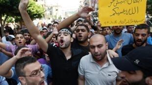 Des manifestants hostiles au régime syrien protestent dans la ville portuaire de Tripoli, au nord du Liban, vendredi 14 octobre 2011.