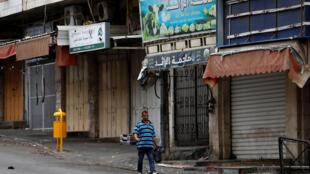 Un palestino camina por una calle comercial durante la huelga contra la Ley Nacional de Israel. Hebrón, 1 de octubre de 2018.