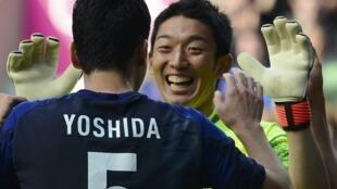 Japan's Maya Yoshida and goalkeeper Shuichi Gonda celebrate a goal during their football match against Morocco, 29 July, 2012