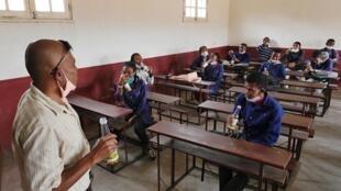 Au lycée public de Nanisana, les élèves de terminale et leur proviseur trinquent au Covid-Organics, la décoction promue par le président pour prévenir et guérir du coronavirus. Un élève par banc au lieu de deux ou trois habituellement, des caches bouches e