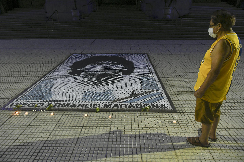 Foto publicada por Télam de un fanático mirando velas encendidas junto a la imagen de la leyenda del fútbol argentino Diego Armando Maradona en el Centro Cultural Kirchner (CCK) en Buenos Aires, a principios del 26 de noviembre de 2020.