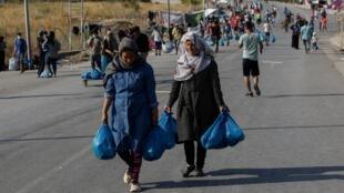 Des réfugiés du camp détruit de Moria partent vers un nouveau camp temporaire, sur l'île de Lesbos, Grèce, 17 septembre 2020.