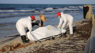 Funcionários da organização Crescente Vermelho recuperam corpo de migrante na praia de Zuara, na Líbia.