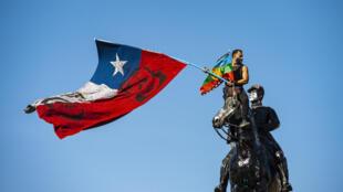 Un manifestante agita banderas desde la cima del monumento General Baquedano en la Plaza Italia, durante una protesta contra el gobierno chileno, el 9 de octubre de 2020 en Santiago