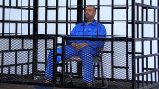 Saif al-Islam Kadhafi attends a hearing behind bars in a courtroom in Zintan in 2014