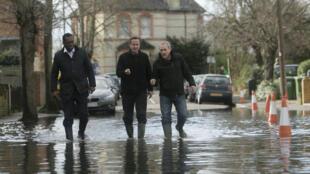 O primeiro-ministro britânico, David Cameron ( centro), caminha na Guildford Street alagada, em Londres