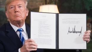 Le président américain Donald Trump arbore la signature du retrait des Etats-Unis de l'accord sur le programme nucléaire en Iran et du rétablissement des sanctions américaines contre Téhéran, le 8 mai 2018, à la Maison Blanche.