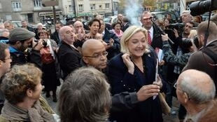 Front National president Marine Le Pen is taken away as a Femen militant is arrested by security staff