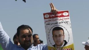 Un manifestant brandit le portrait du journaliste Mohammed al-Qiq, près de Ramallah lors d'une manifestation, le 19 février 2016.