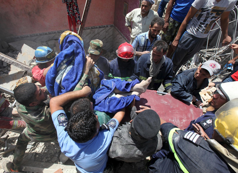 """Equipes de resgate carregam um corpo encontrado nos escombros de residências destruídas no """"bombardeio acidental"""" em Bagdá nesta segunda-feira (6)."""