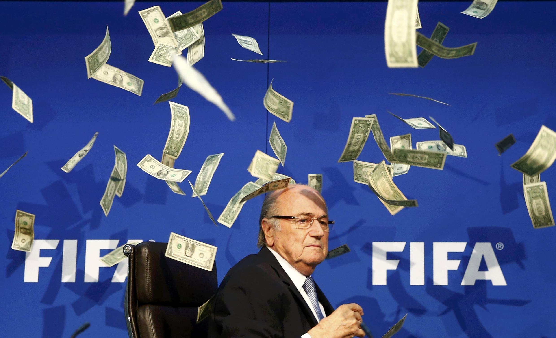 Sepp Blatter, presidente demissionário da FIFA, numa conferência de imprensa perturbada por um comediante britânico que atirou dinheiro falso.