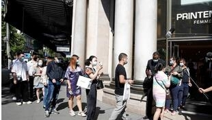 People, wearing protective face masks, clean their hands with disinfectant before entering inside the department store Le Printemps Haussmann in Paris as France eases gradually its lockdown measures and restrictions following the outbreak of the coronavirus disease (COVID-19) in France, May 28, 2020.
